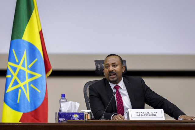 FILE - In this file photo dated Monday, Nov. 30, 2020, Ethiopia's Prime Minister Abiy Ahmed responds to questions from members of parliament at the prime minister's office in the capital Addis Ababa, Ethiopia. A new report from the Ethiopian Human Rights Commission published Friday Jan. 1, 2021, says Ethiopian security forces killed more than 75 people and injured nearly 200 during deadly unrest in June and July after the killing of a popular singer.  Ethnic violence is a major challenge to Nobel Peace Prize-winning Prime Minister Abiy Ahmed, who has urged national unity. (AP Photo/Mulugeta Ayene, FILE)