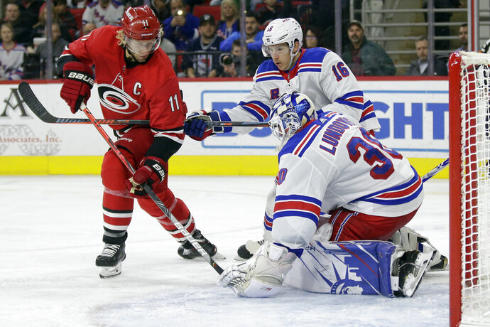New York Rangers goaltender Henrik Lundqvist (30), of Sweden, blocks Carolina Hurricanes center Jordan Staal (11) while Rangers center Ryan Strome (16) helps defend during the second period of an NHL hockey game in Raleigh, N.C., Thursday, Nov. 7, 2019. (AP Photo/Gerry Broome)
