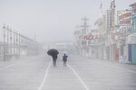 A man shields himself from the rain with an umbrella as he walks along with a child during a rainy and foggy winter afternoon at the Ocean City boardwalk in Ocean City, N.J. (Jose F. Moreno/The Philadelphia Inquirer via AP)