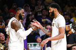 Los Angeles Lakers' LeBron James, left, celebrates with teammate Anthony Davis during a timeout in the second half of an NBA basketball game, Sunday, Dec. 8, 2019, in Los Angeles. The Lakers won 142-125. (AP Photo/Ringo H.W. Chiu)