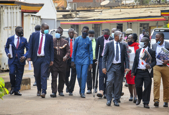 Ugandan opposition presidential candidate Bobi Wine, center, leaves with party officials after a meeting at the Electoral Commission in Kampala, Uganda Wednesday, Dec. 2, 2020. Wine said Wednesday after meeting the head of the country's electoral body that he would resume his campaign after suspending it in protest over police brutality after police shot his car tires and fired rubber bullets that injured his bodyguards and supporters. (AP Photo/Ronald Kabuubi)