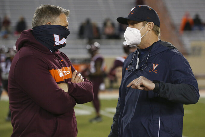 Virginia Tech coach Justin Fuente, left, and Virginia coach Bronco Mendenhall talk before an NCAA college football game Saturday, Dec. 12, 2020, in Blacksburg, Va. (Matt Gentry/The Roanoke Times via AP, Pool)