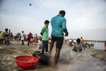 A man wearing a mask as a precaution against COVID-19 watches fishermen clear their nets on the Arabian Sea coast in Kochi, Kerala state, India, Monday, Sept.20, 2021. The tiny southern state continues to battle the highest number of coronavirus cases in the country. (AP Photo/R S Iyer)