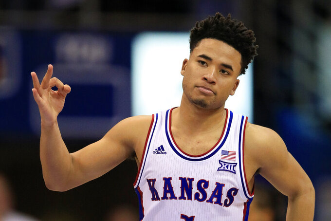 FILE - In this March 4, 2020, file photo, Kansas guard Devon Dotson celebrates a 3-point basket during the second half of the team's NCAA college basketball game against TCU, in Lawrence, Kan. Dotson was selected to the Associated Press All-Big 12 first team announced Tuesday, March 10, 2020.(AP Photo/Orlin Wagner, File