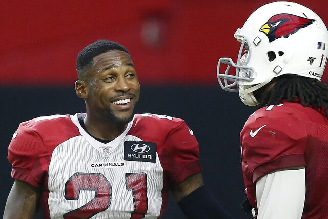 FILE - In this Aug. 6, 2019, file photo, Arizona Cardinals cornerback Patrick Peterson (21), left, and Cardinals wide receiver Larry Fitzgerald talk during an NFL football training camp practice at State Farm Stadium in Glendale, Ariz. Peterson believes the team can be among the NFL's elite this fall. Peterson is in the final year of a five-year contract and hopes to stay with the Cardinals for the remainder of his career. (AP Photo/Ross D. Franklin, File)