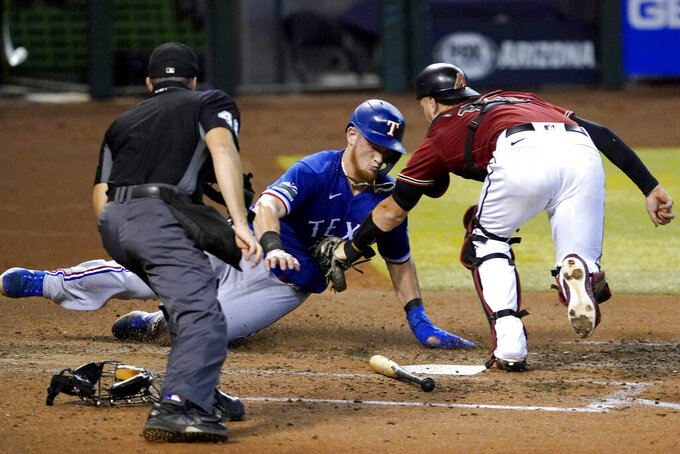 Texas Rangers' Sam Huff is tagged out at the plate by Arizona Diamondbacks catcher Carson Kelly while trying to score on a fielders choice hit by teammate Anderson Tejeda during the sixth inning of a baseball game, Wednesday, Sept. 23, 2020, in Phoenix. (AP Photo/Matt York)