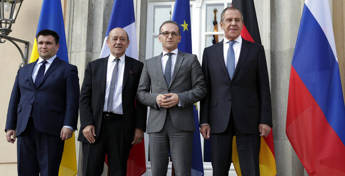 From left, the foreign ministers from Ukraine, Pavlo Klimkin, France, Jean-Yves Le Drian, Germany, Heiko Maas, and Russia, Sergey Lavrov, pose for the media prior to a meeting in Berlin, Germany, Monday, June 11, 2018. (AP Photo/Michael Sohn)
