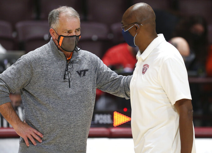 Virginia Tech head coach Mike Young, left,and Radford head coach Mike Jones talk at the conclusion of  an NCAA college basketball game, Wednesday Nov. 25, 2020, in Blacksburg Va. (Matt Gentry/The Roanoke Times via AP)