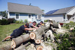 From left to right, Grant Whitmore, Jason Kirk and Peter Delaney roll a tree trunk while cutting it apart at Whitmore's home in northwest Cedar Rapids, Iowa, on Wednesday, Aug. 12, 2020. Straight-line winds on Monday knocked out power, trees and damaged homes and businesses region-wide. (Liz Martin/The Gazette via AP)