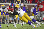 "FILE - LSU nose tackle Tyler Shelvin (72) tackles Mississippi wide receiver Elijah Moore (8) during the second half of an NCAA college football game in Oxford, Miss., Saturday, Nov. 16, 2019. LSU coach Ed Orgeron says defensive lineman Neil Farrell has rejoined the team after initially opting out more than a month ago. Orgeron says he's also hearing ""rumblings"" that defensive lineman Tyler Shelvin could opt back. (AP Photo/Thomas Graning, File)"
