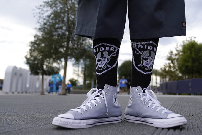 A Las Vegas Raiders poses in front of SoFi stadium before an NFL football game against the Los Angeles Chargers, Monday, Oct. 4, 2021, in Inglewood, Calif. (AP Photo/Marcio Jose Sanchez)