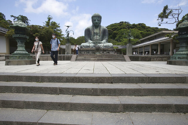 People wearing face masks to protect against the spread of the new coronavirus visit The Great Buddha statue at Kotoku-in Temple in Kamakura, near Tokyo Tuesday, June 2, 2020. Japanese Prime Minister Shinzo Abe announced the lift of a coronavirus state of emergency from Tokyo and four other remaining areas last week, ending the restrictions nationwide as businesses begin to reopen. (AP Photo/Koji Sasahara)