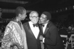 FILE - In this July 10, 1984, file photo, Felix Rohatyn, center, is surrounded by Judith Jamison and Alvin Ailey during a champagne supper at the New York State Theater in New York, to honor Rohatyn for his contribution to the cultural and business life of New York City. A banker who was credited with saving New York City from financial ruin, Rohatyn died Saturday, Dec. 14, 2019, at his home in Manhattan. He was 91. (AP Photo/Rene Perez, File)
