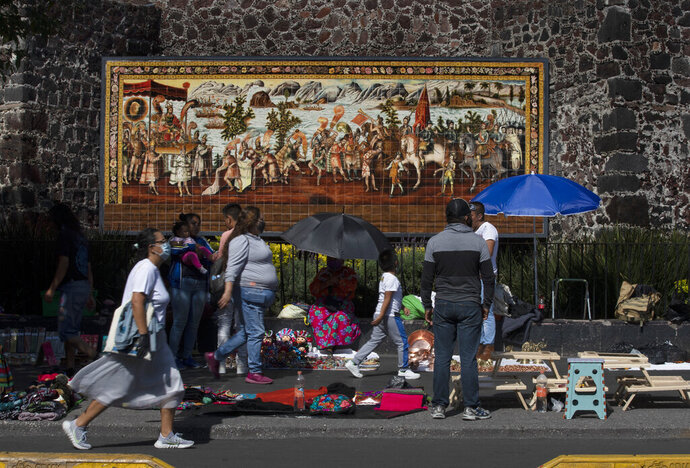 Locals walk past a mural dedicated to Spanish Conquistador Hernan Cortes, in Mexico City, Monday, Sept. 28, 2020. Smallpox was brought to Mexican lands by the Spanish and played a significant role in the downfall of the Aztec Empire Smallpox and other newly introduced diseases went on to kill tens of millions of Indigenous people in the Americas who had no resistance to the European illnesses. (AP Photo/Marco Ugarte)
