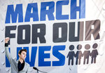FILE- In this March 24, 2018 file photo, David Hogg, a survivor of the mass shooting at Marjory Stoneman Douglas High School in Parkland, Fla., raises his fist after speaking during the