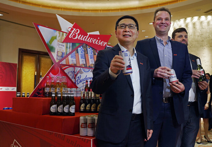 From left, Frank Wang, Executive Director, Jan Craps, Executive Director and CEO and Guilherme Castellan, Chief Financial Officer of Budweiser Brewing Company APAC Limited pose with products in Hong Kong Tuesday, Sept. 17, 2019. AB InBev, the world's largest brewer that produces Budweiser and Corona, has revived plans to list its Asian business in Hong Kong despite persistent pro-democracy protests but halved the size of its initial public offering. (AP Photo/Vincent Yu)