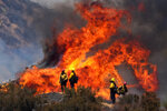 Firefighters watch the Apple Fire in Banning, Calif., Sunday, Aug. 2, 2020. (AP Photo/Ringo H.W. Chiu)