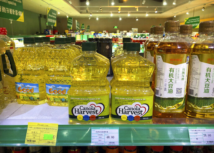 Bottles of Canola Harvest brand canola oil, manufactured by Canadian agribusiness firm Richardson International, are seen on the shelf of a grocery store in Beijing, Wednesday, March 6, 2019. One of Canada's largest grain processors said Tuesday that China has revoked its permit to export canola there, a move that some saw as retaliation for the Canadian government's arrest of a top executive for the Chinese tech giant Huawei. (AP Photo/Mark Schiefelbein)