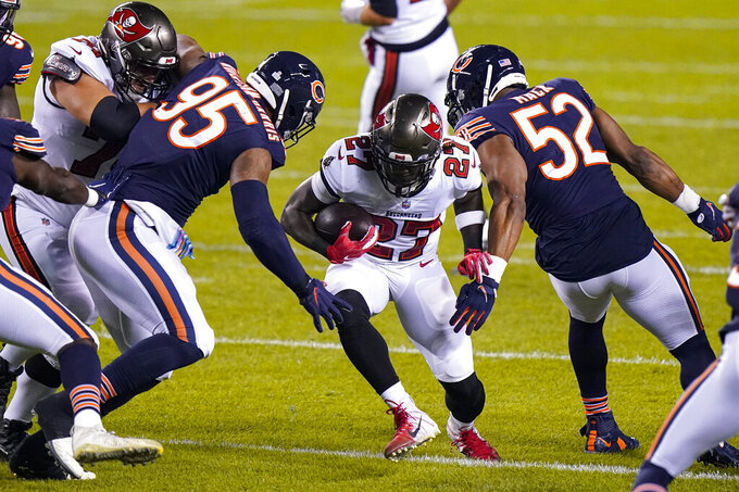 Tampa Bay Buccaneers running back Ronald Jones (27) cuts between Chicago Bears defensive end Roy Robertson-Harris (95) and outside linebacker Khalil Mack (52) during the first half of an NFL football game in Chicago, Thursday, Oct. 8, 2020. (AP Photo/Nam Y. Huh)
