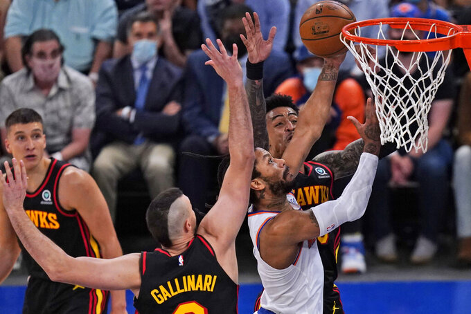 New York Knicks' Derrick Rose, second from right, makes a basket during the first half of Game 1 of an NBA basketball first-round playoff series against the Atlanta Hawks, Sunday, May 23, 2021, in New York. (AP Photo/Seth Wenig, Pool)