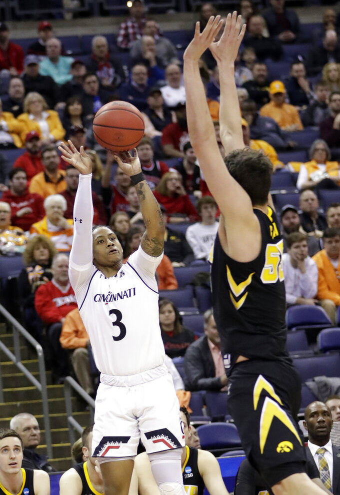 Cincinnati's Justin Jenifer (3) shoots over Iowa's Luka Garza (55) in the first half during a first round men's college basketball game in the NCAA Tournament in Columbus, Ohio, Friday, March 22, 2019. (AP Photo/Tony Dejak)