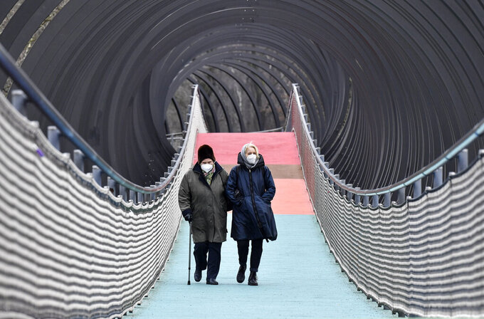 "FILE - In this Monday, Jan. 11, 2021 file photo,People wear protective face masks due to the coronavirus pandemic, as they walk over a bridge during the lockdown in Oberhausen, Germany. Armin Laschet, a governor who also leads Merkel's party, called this week for a vaguely defined 2-3 week ""bridge lockdown"" to control infections while Germany steps up a so-far slow vaccination campaign. German Chancellor Angela Merkel has thrown her weight behind calls for a 'short, uniform lockdown'. (AP Photo/Martin Meissner, file)"