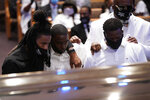 Mourners pause by the casket of George Floyd during a funeral service for Floyd at The Fountain of Praise church Tuesday, June 9, 2020, in Houston. (AP Photo/David J. Phillip, Pool)