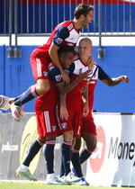 FC Dallas midfielder Ryan Hollingshead (12) jumps onto teammates surrounding orward Zdenek Ondrasek (13) after Ondrasek scored the first goal of an MLS soccer match during the first half against Sporting Kansas City in Frisco, Texas, Sunday, Oct. 6, 2019. (Stewart F. House/The Dallas Morning News via AP)