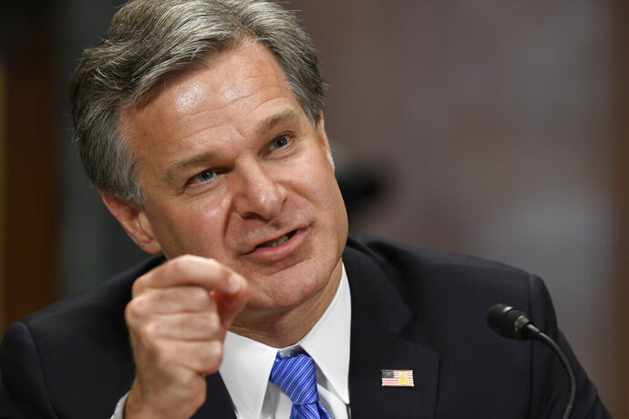 """FILE - In this July 23, 2019 file photo, FBI Director Christopher Wray testifies before the Senate Judiciary Committee on Capitol Hill in Washington.  Wray says there is """"a way forward"""" to allow police officers to wear body cameras on federal task forces while speaking at the International Association of Chiefs of Police conference in Chicago, Saturday, Oct. 26. His affirmation the FBI will seek to reverse its current policy banning officers from wearing the body-worn cameras on joint operations with federal agents comes months after Atlanta's police chief withdrew city police officers from federal task forces over the issue.(AP Photo/Susan Walsh, File)"""