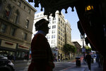 In this photo taken Monday, Jan. 6, 2020, Beefeater doorman Tom Sweeney is silhouetted while standing outside the Sir Francis Drake Hotel in San Francisco. Sweeney has opened doors for movie stars and shaken hands with every U.S. president since Gerald Ford, with the exception of Donald Trump. He's taken photos with countless visitors from around the world, often after telling them where to catch the cable car and how to get to Fisherman's Wharf. The man known as a