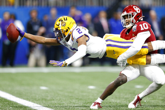 LSU wide receiver Justin Jefferson (2) extends for a touchdown while Oklahoma safety Pat Fields (10) attempts to tackle him during the first half of the Peach Bowl NCAA college football playoff semifinal in Atlanta on Saturday, Dec. 28, 2019. (Ian Maule/Tulsa World via AP)