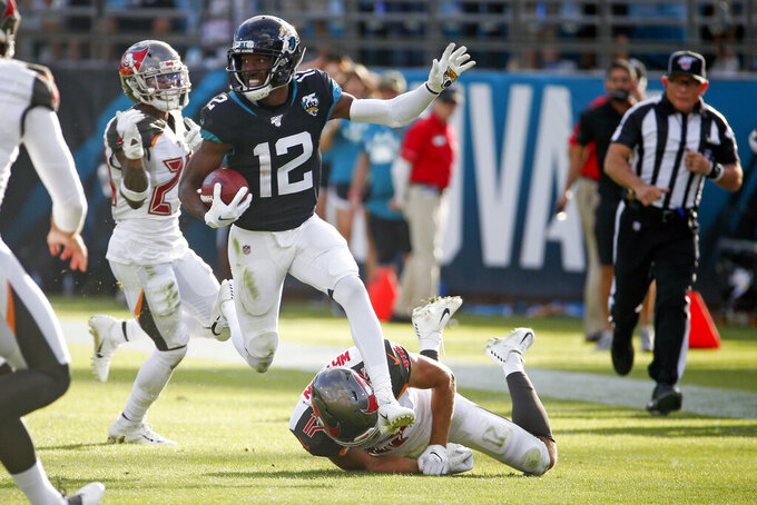 Jacksonville Jaguars' Dede Westbrook (12) returns a punt as Tampa Bay Buccaneers'Justin Watson, lower right, tries to stop him during the second half of an NFL football game, Sunday, Dec. 1, 2019, in Jacksonville, Fla. (AP Photo/Stephen B. Morton)
