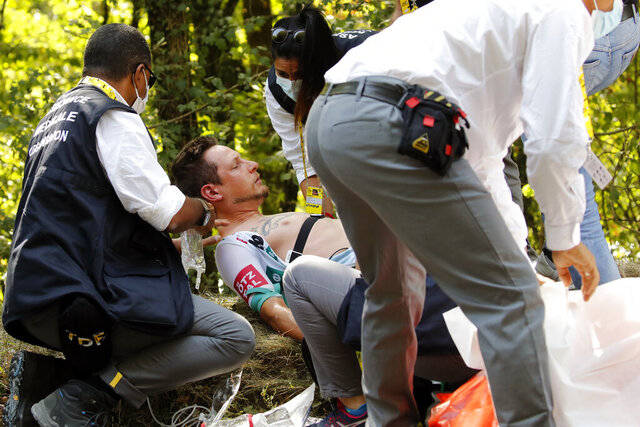 Lukas Postlberger of Austria is treated by medics during the stage 19 of the Tour de France cycling race over 166 kilometers (103 miles), with start in Bourg-en-Bresse and finish in Champagnole, Friday, Sept. 18, 2020. (AP Photo/Christophe Ena)