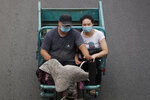 A couple wearing face masks to help protect against the coronavirus ride on a tricycle-cart in Beijing, Thursday, Aug. 6, 2020. China's biggest recent outbreak of coronavirus has grown slightly. Hundreds people have developed COVID-19 in the far northwestern region of Xinjiang, with more than dozens of new cases reported Thursday in its capital and largest city, Urumqi. (AP Photo/Andy Wong)