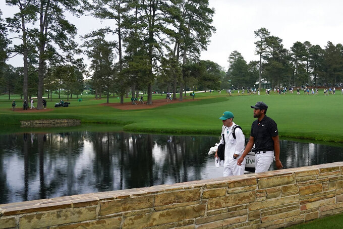 Tony Finau walks across the Sarazen Bridge with his caddie Mark Urbanek on the 15th hole during the third round of the Masters golf tournament on Saturday, April 10, 2021, in Augusta, Ga. (AP Photo/Matt Slocum)