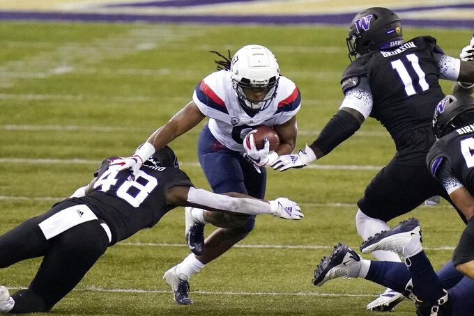 Arizona running back Gary Brightwell, center, runs as Washington's Edefuan Ulofoshio (48) and Josiah Bronson (11) move in during the first half of an NCAA college football game Saturday, Nov. 21, 2020, in Seattle. (AP Photo/Elaine Thompson)