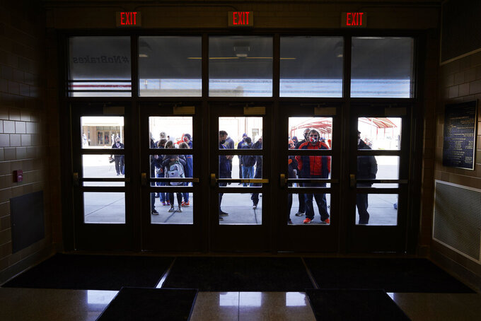 Basketball fans wait outside the Indiana Farmers Coliseum before a first round NCAA college basketball game between Illinois and Drexel Friday, March 19, 2021, in Indianapolis. (AP Photo/Charles Rex Arbogast)