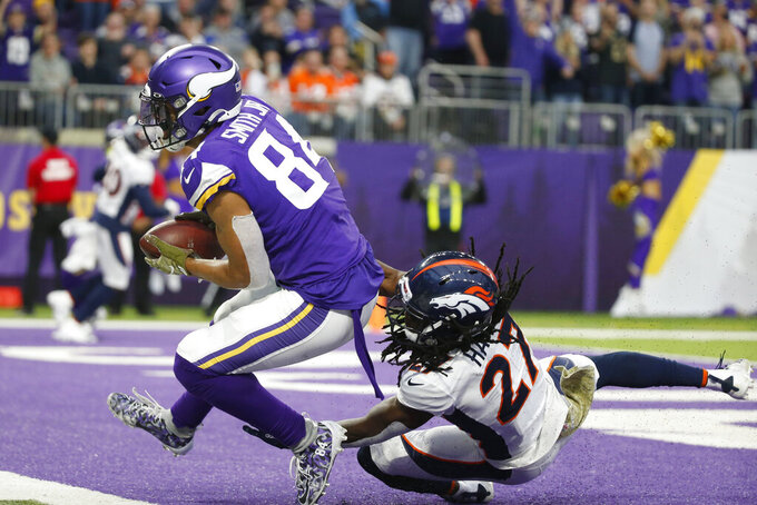 Minnesota Vikings tight end Irv Smith (84) catches a 10-yard touchdown pass ahead of Denver Broncos cornerback Davontae Harris, right, during the second half of an NFL football game, Sunday, Nov. 17, 2019, in Minneapolis. (AP Photo/Bruce Kluckhohn)