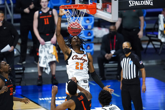 Oklahoma State forward Kalib Boone (22) dunks on Oregon State forward Maurice Calloo (1) during the first half of a men's college basketball game in the second round of the NCAA tournament at Hinkle Fieldhouse in Indianapolis, Sunday, March 21, 2021. (AP Photo/Paul Sancya)