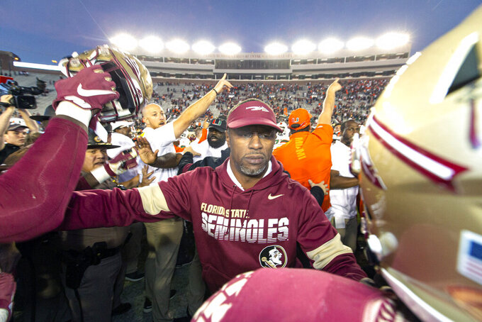 Florida State head coach Willie Taggart, center, tries to separate his team from the Miami team at midfield after Miami defeated Florida State in an NCAA college football game in Tallahassee, Fla., Saturday, Nov. 2, 2019. (AP Photo/Mark Wallheiser)