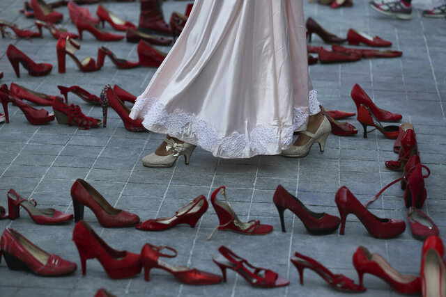 An actress walks near a line of red shoes representing murdered women, as part of a performance during the International Women's Day strike