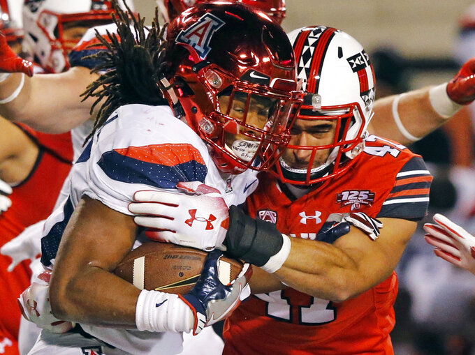 Arizona running back Gary Brightwell, left, is tackled by Utah defensive end Caleb Repp, right, in the second half during an NCAA college football game Friday, Oct. 12, 2018, in Salt Lake City. (AP Photo/Rick Bowmer)