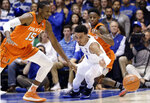 Duke's Tre Jones and Miami's Ebuka Izundu (15) chase the ball during the first half of an NCAA college basketball game in Durham, N.C., Saturday, March 2, 2019. Miami's Chris Lykes looks on at rear. (AP Photo/Gerry Broome)