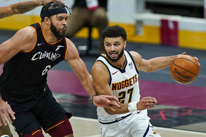 Denver Nuggets' Jamal Murray (27) drives past Cleveland Cavaliers' JaVale McGee (6) during the second half of an NBA basketball game Friday, Feb. 19, 2021, in Cleveland. (AP Photo/Tony Dejak)