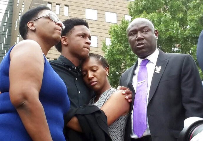 FILE - In this Sept. 10, 2018 file photo, Brandt Jean, center left, brother of shooting victim Botham Jean, hugs his sister Allisa Charles-Findley, during a news conference about the shooting of Botham Jean by Dallas Police Officer Amber Guyger, outside the Frank Crowley Courts Building in Dallas. He was joined by his mother, Allison Jean, left, and attorney Benjamin Crump, right. Guyger, who was fired soon after the shooting and charged with murder, said she mistook Jean's apartment for her own. She was convicted in early Oct. 2019 — a rare jury decision — and sentenced to 10 years in prison. (AP Photo/Ryan Tarinelli, File)