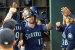 Seattle Mariners' Mitch Haniger is congratulated in the dugout after hitting a three run home run against the Texas Rangers that scored Jake Bauers and J.P. Crawford during the second inning of a baseball game Thursday, Aug. 19, 2021, in Arlington, Texas. (AP Photo/Jeffrey McWhorter)