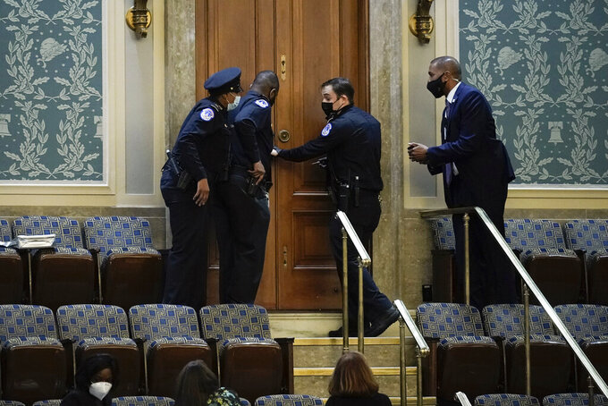 FILE - In this Jan. 6, 2021, file photo U.S. Capitol Police secure a door as rioters try to break into the House Chamber at the U.S. Capitol in Washington. (AP Photo/J. Scott Applewhite, File)