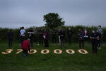 Campaigners attend a vigil to remember the millions who have died during the COVID-19 pandemic, organised by 'Crack the Crisis Coalition' in Falmouth, Cornwall, England, Friday, June 11, 2021. Leaders of the G7 began their first of three days of meetings on Friday in Carbis Bay, in which they will discuss COVID-19, climate, foreign policy and the economy. (AP Photo/Kirsty Wigglesworth)
