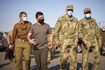 FILE In this file photo taken on Saturday, Sept. 26, 2020, Ukrainian President Volodymyr Zelenskiy, second left, surrounded by servicemen as he visits the war-hit Donetsk region, eastern Ukraine. Ukrainians are heading to the polls on Sunday, Oct. 25, 2020 to cast ballots in local elections seen as a key test for President Volodymyr Zelenskiy. Zelenskiy, a popular comedian without prior political experience, was elected by a landslide in April 2019 on promises to end fighting with Russia-backed separatists in eastern Ukraine, uproot endemic corruption and shore up a worsening economy.(Ukrainian Presidential Press Office via AP, File)
