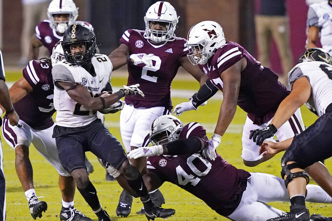 Vanderbilt running back Keyon Henry-Brooks (21) is pursued by a number of Mississippi State defenders, including linebacker Erroll Thompson (40), during the second half of an NCAA college football game in Starkville, Miss., Saturday, Nov. 7, 2020. (AP Photo/Rogelio V. Solis)